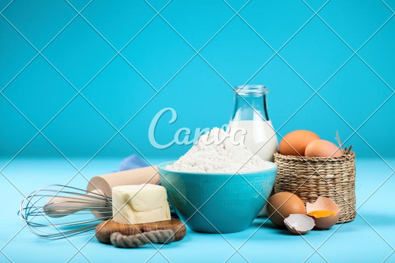 Basic Baking Ingredients on BLue Background - Photos by Canva
