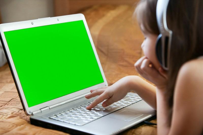 Photo Kid's Hands typing keyboard on desk wood.