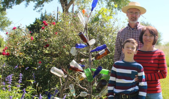 Eli with mom Becky and dad Stan in front of a bottle tree that they made by wiring together old Christmas Tree trunks