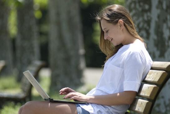 公園で笑顔でパソコンを見る女性