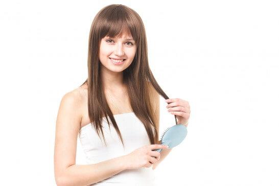 クシで髪の毛をとかす女性