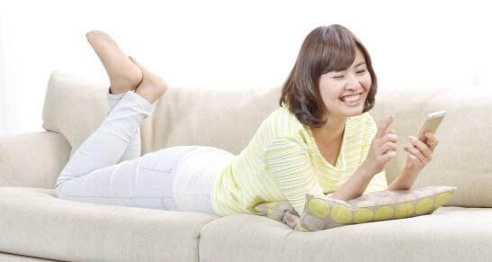 寝そべりながらスマートフォンを操作する女性