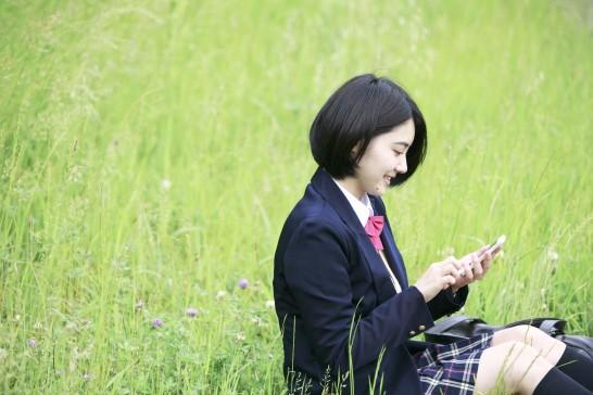 携帯電話を見る女子高生