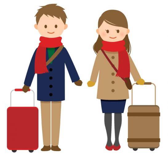 スーツケースを持つ男女