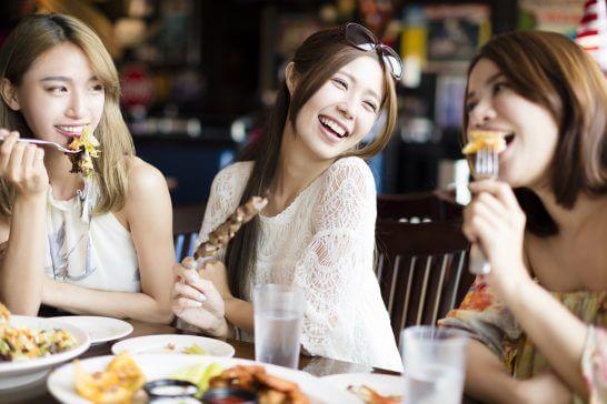 レストランで食事をする笑顔の女性