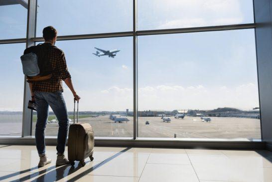 空港で飛行機を見つめる男性