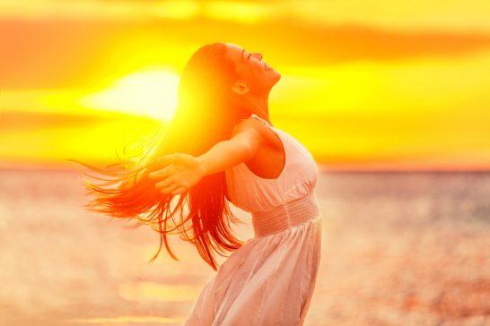 日差しの中手を広げる女性