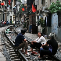 Vietnamese family drinking tea on railtracks in Hanoi, Vietnam