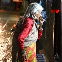 Nepal old woman smoking in the night