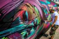 Street artist Hopare at work on one of his colorful ...