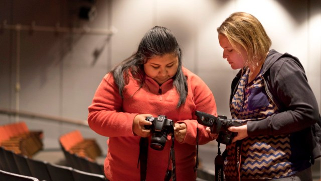 Rocio Pulido-Rosales. left, and Jennifer Sonnon compare results while learning to use off-camera flash in a location photography class at MTCC. ©2018 Christopher Jayne