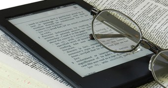 E-reader on book with glasses