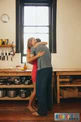 Happy young woman being hugged by her boyfriend in the kitchen. Cheerful young couple embracing each other in morning at home.