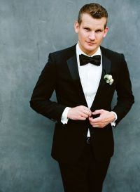 groom in black suit and black bow tie...