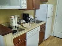 Full kitchenette with dishwasher, plates, glasses, pans ...