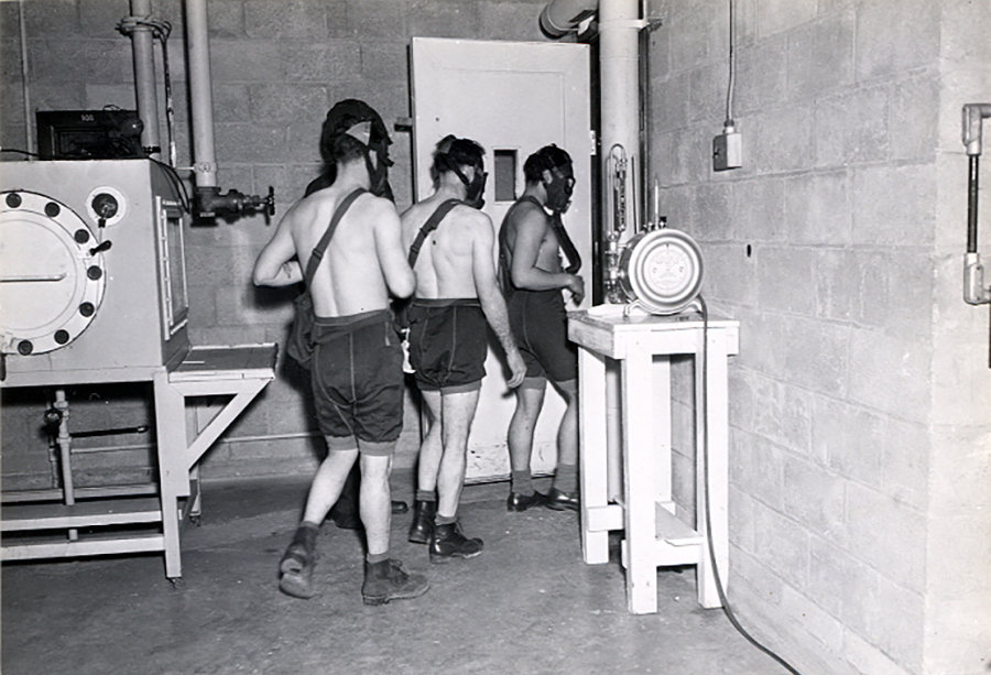 Three test subjects enter a gas chamber, which will fill with mustard gas, as part of the military's secret chemical warfare testing in March 1945. Courtesy of Edgewood Arsenal