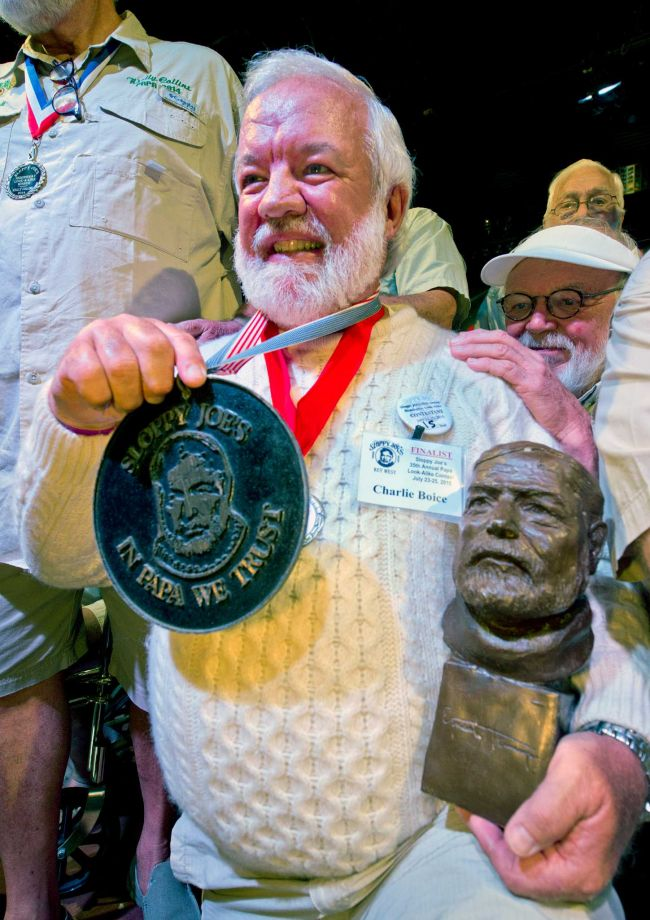 """In this Saturday, July 25, 2015 photo provided by the Florida Keys News Bureau, Charlie Boice beams after winning the 2015 """"Papa"""" Hemingway Look-Alike Contest at Sloppy Joe's Bar in Key West, Fla. Boice finally won the contest after 15 attempts, beating out 121 other entrants following two preliminary rounds, semi-finals and two final rounds. The competition was a facet of the subtropical island's annual Hemingway Days festival that ends Sunday, July 26. Ernest Hemingway lived and wrote in Key West throughout the 1930s. (Andy Newman/Florida Keys News Bureau)"""