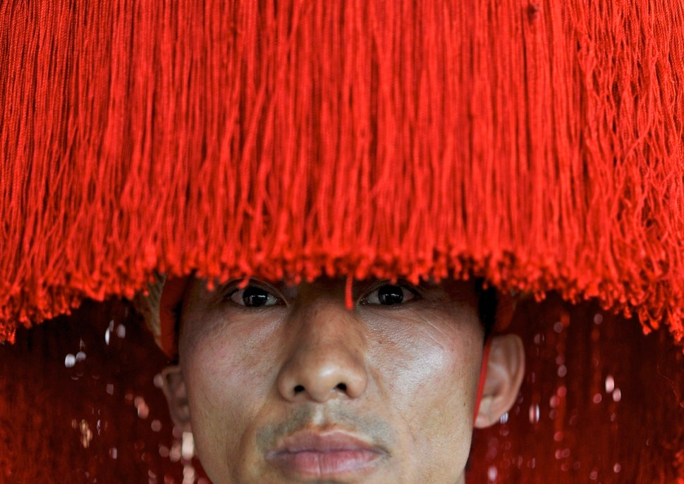 A Tibetan exile, wearing a traditional headdress, attends the Jangchup Lamrim teachings conducted by the exiled Tibetan spiritual leader the Dalai Lama (unseen) at the Gaden Jangtse Thoesam Norling Monastery at Mundgod in the southern Indian state of Karnataka December 26, 2014. REUTERS/Abhishek N. Chinnappa (INDIA - Tags: RELIGION SOCIETY TPX IMAGES OF THE DAY) - RTR4JAMX
