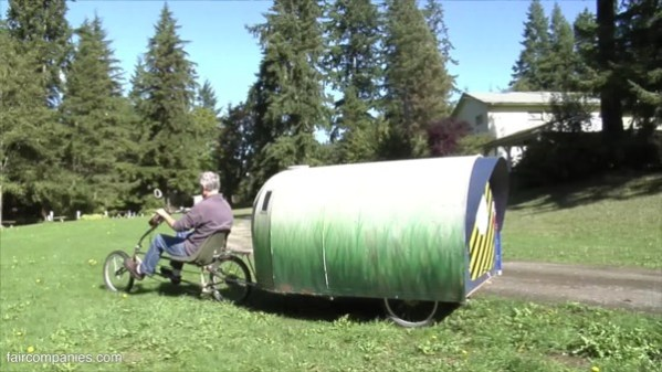 Cozy $150 micro-camping trailer pulled by bike has kitchen, bed, bookshelves