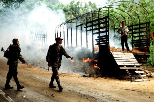 Two colombian soldiers patrol in front at a truck burned by rebels of the Revolutionary Armed Forces of Colombia (FARC) in Cisneros, 80 kms west from Cali, Valle del Cauca province March 6, 2002. REUTERS/Juan B. Diaz