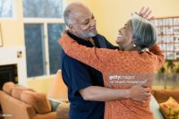 African American Couple Dancing In Living Room Stock Photo