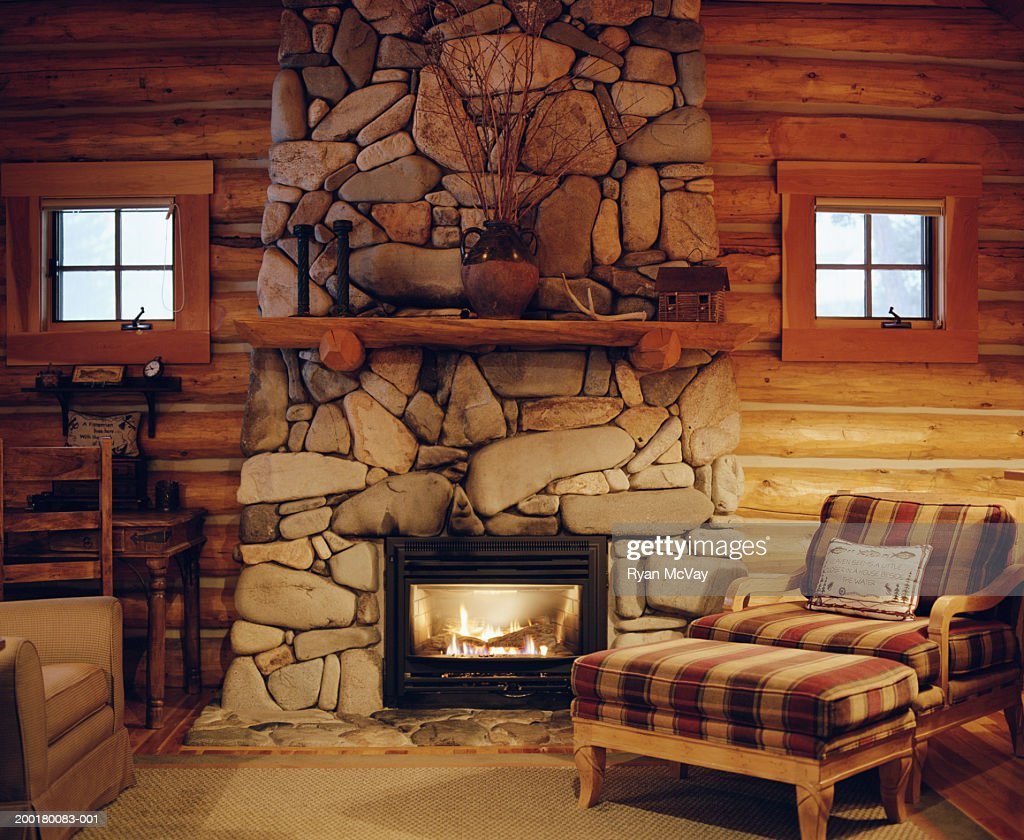Fall Ceiling Wallpaper Armchair Beside Stone Fireplace In Log Cabin Stock Photo