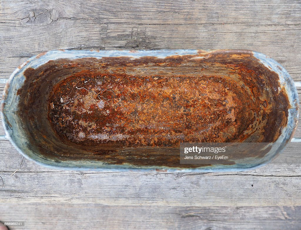 Schwarz Container Directly Above Shot Of Rusty Container On Wooden Table Stock Photo