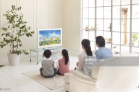 A Family Watching Tv In The Living Room Stock Photo ...