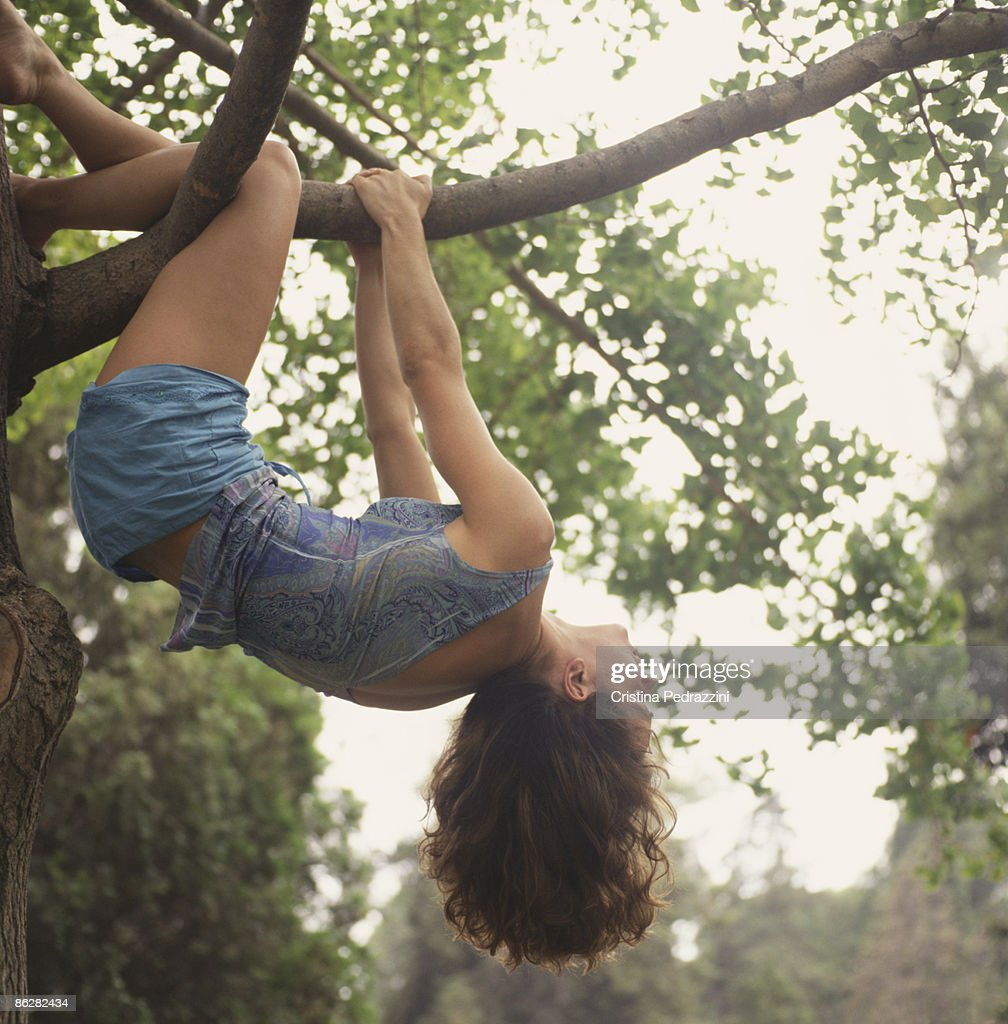 Girl Hanging Upside Down From Tree Branch Stock Photo | Getty Images