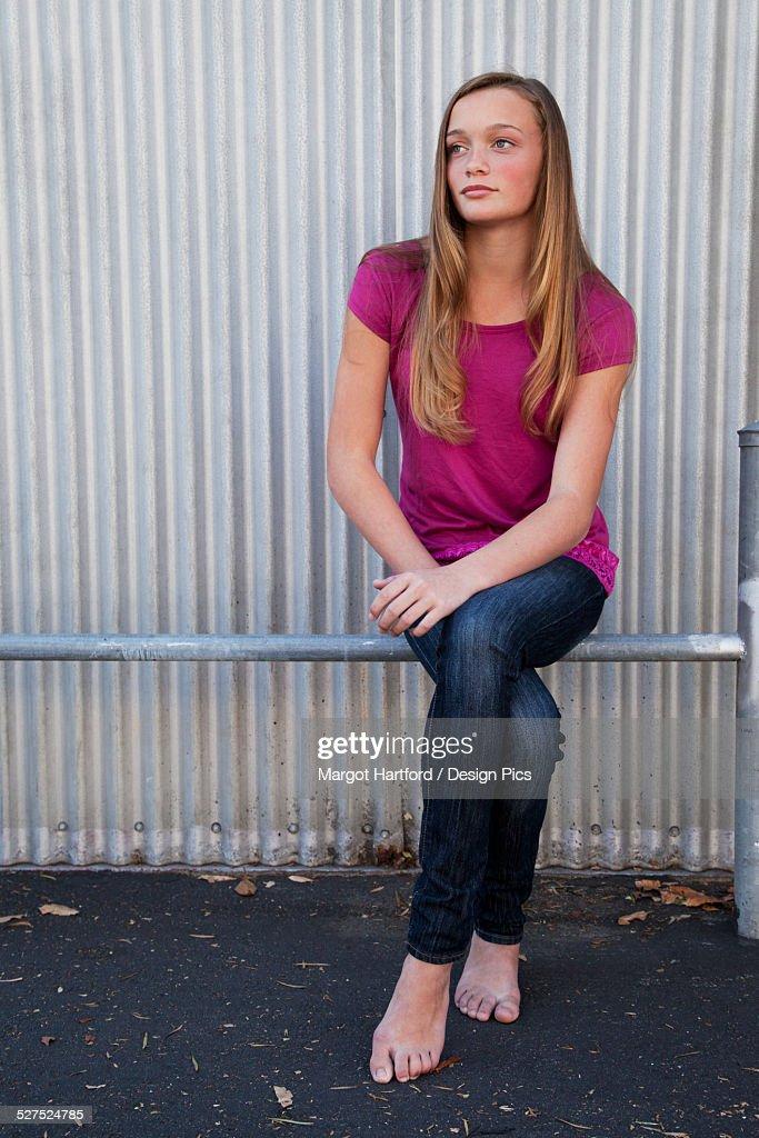 Cute Lockets Wallpaper A Girl Sitting On A Metal Rail In Bare Feet Stock Photo