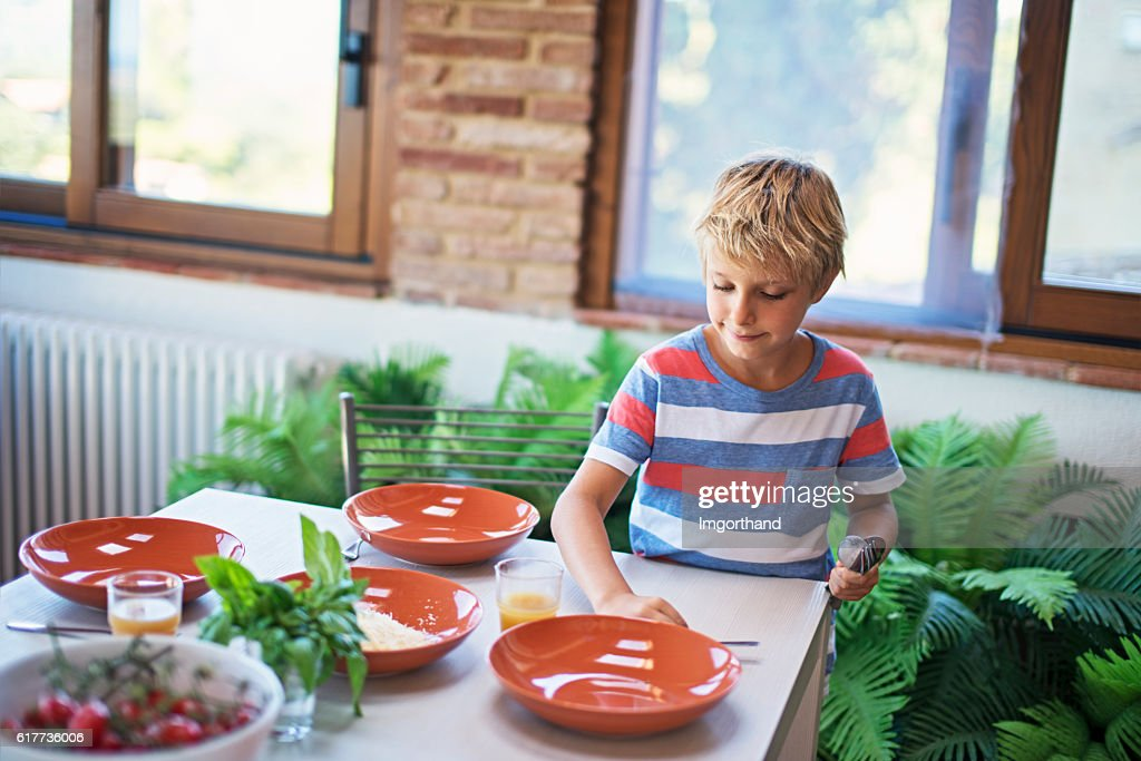 Little Boy Setting Up Table For Family Lunch Stock Photo