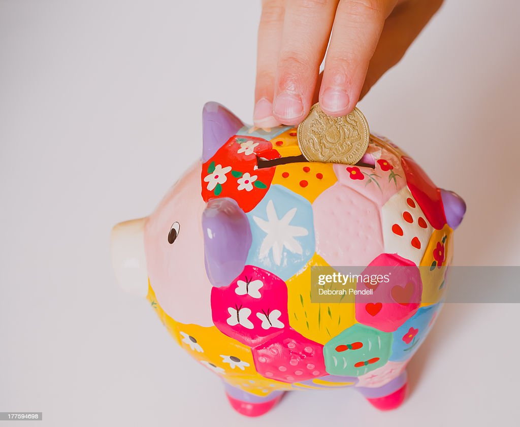 Piggy Bank Adult Money Going In A Piggy Bank Stock Photo Getty Images