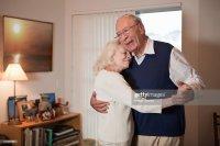 Senior Couple Dancing In Living Room Stock Photo