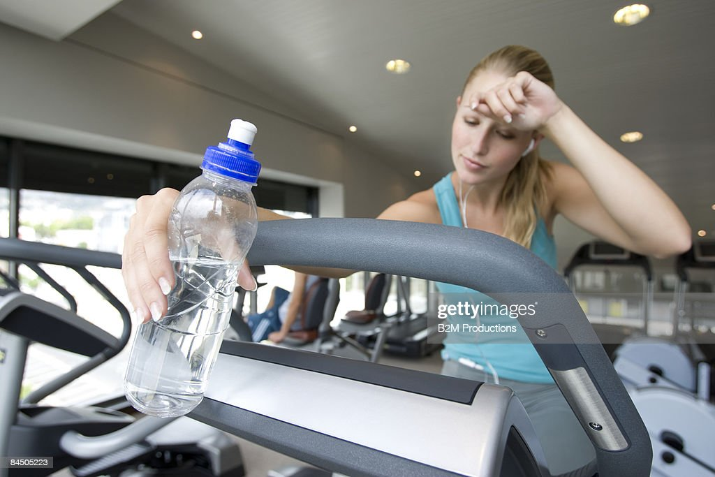 Sport Mat Woman With Bottle Of Water Using Exercise Bike Stock Photo
