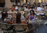 Women smoking a waterpipe on a cafe terrace in downtown ...