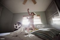 Young Girl Jumping On The Bed With A Dog Stock Photo ...