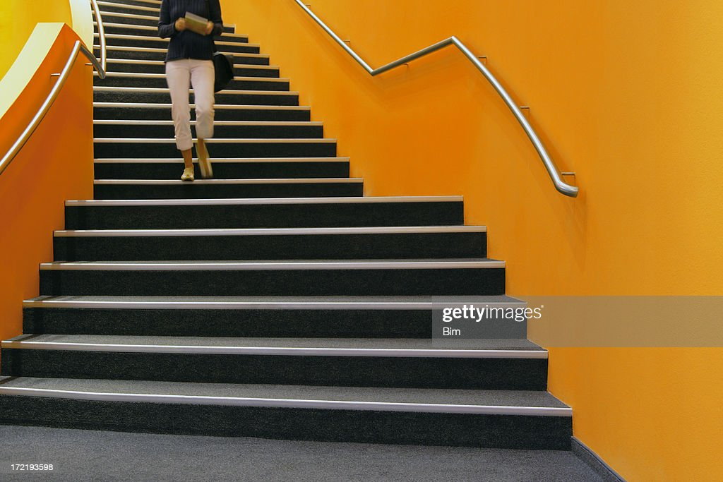 Young Woman Walking Down Orange Stairs Reading Book Stock