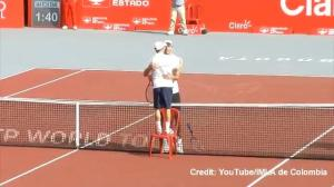 Tennis player stands on chair for post-match hug with much taller opponent