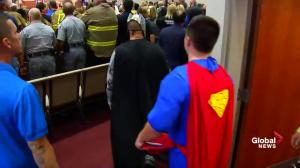 Procession of superhero-clad mourners arrive at funeral for Jacob Hall