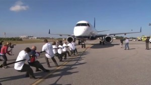 Special Olympics athletes team up with WWE stars to break plane pulling record