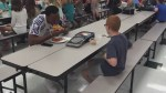 Football player sits with autistic student eating lunch alone