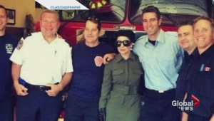 Lady gaga posing with Toronto firefighters