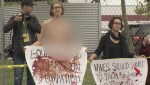 Topless protestor waits for Harper at election platform announcement