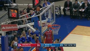 Boy climbs basketball hoop at U.S. college game to retrieve stuck ball
