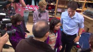 Justin Trudeau helps out a pair of twin sisters with their new winter jackets as they arrive in Canada