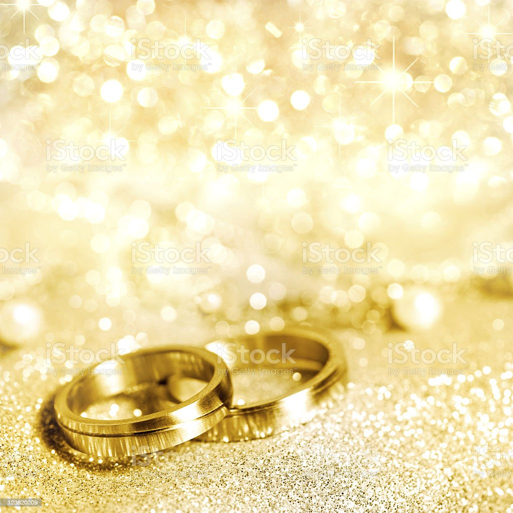 gold wedding rings with glittering gold background gm gold wedding rings Gold wedding rings with glittering gold background royalty free stock photo