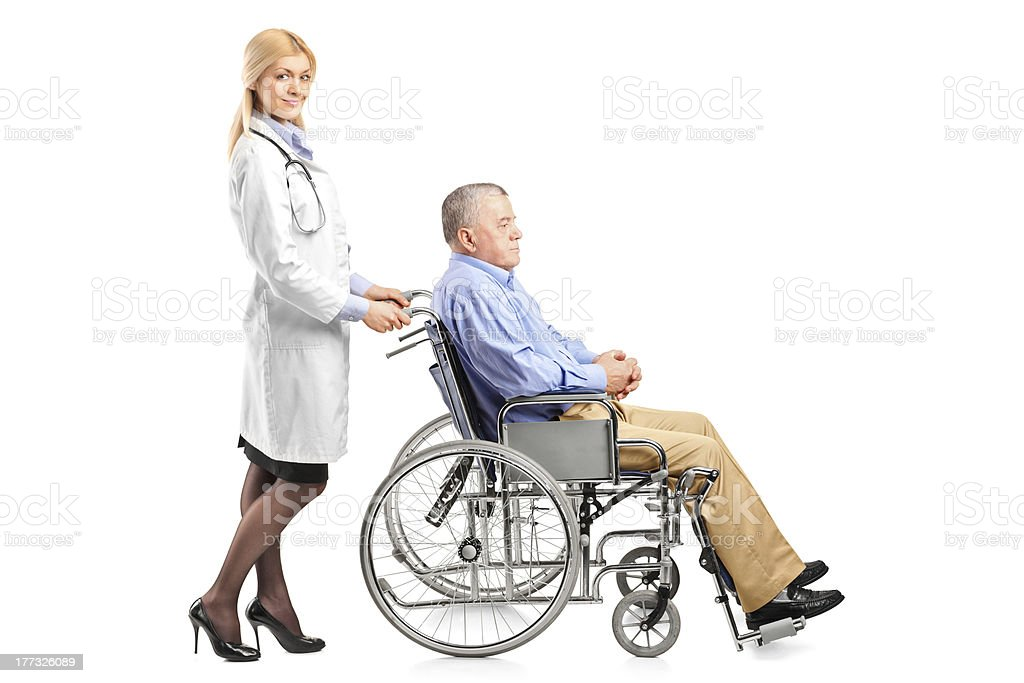 Royalty Free Portrait Of Nurse Pushing Senior Man In
