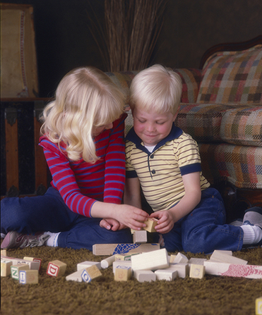 Girl And Boy Sitting Together Wallpaper Playing With Blocks