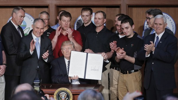 President Donald Trump (center), accompanied by coal miners and (from left) Interior Secretary Ryan Zinke, Environmental Protection Agency (EPA) Administrator Scott Pruitt, Energy Secretary Rick Perry and Vice President Mike Pence holds up the signed Energy Independence Executive Order, March 28, 2017, at EPA headquarters in Washington, D.C. Photo by: AP Photo/Pablo Martinez Monsivais