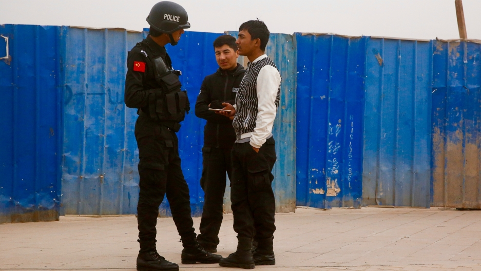 A Chinese police officer talks to men in a street in the city of Kashgar, in the Xinjiang Uighur Autonomous Region of China, on March 24, 2017.